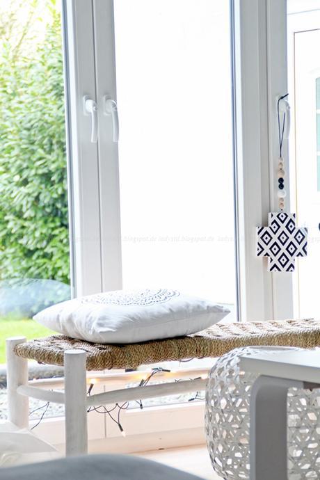Bast Sitzbank Mit Großem Weißen Bast Windlicht Vor Einem Lichtdurchfluteten  Fenster