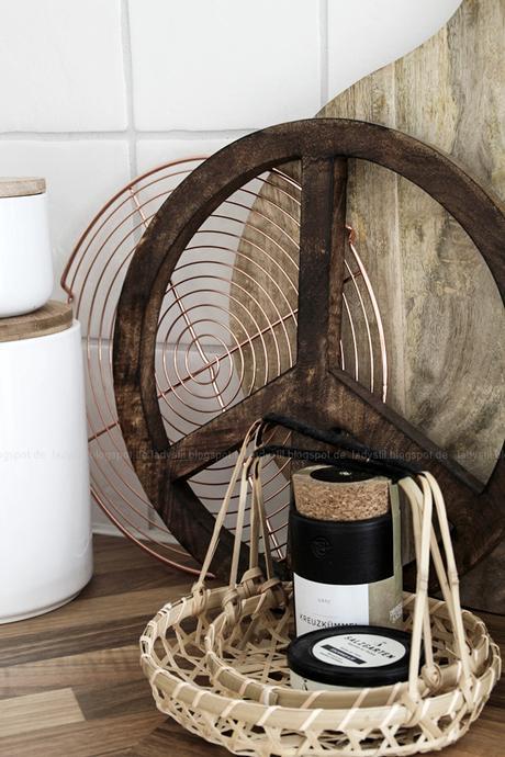 Kücheneinrichtung in Schwarz Weiß Holz mit leichten New Boho Elementen, Detailaufnahme Kuchengitter in Kupfer, Peacezeichen aus Holz und Bambuskörben