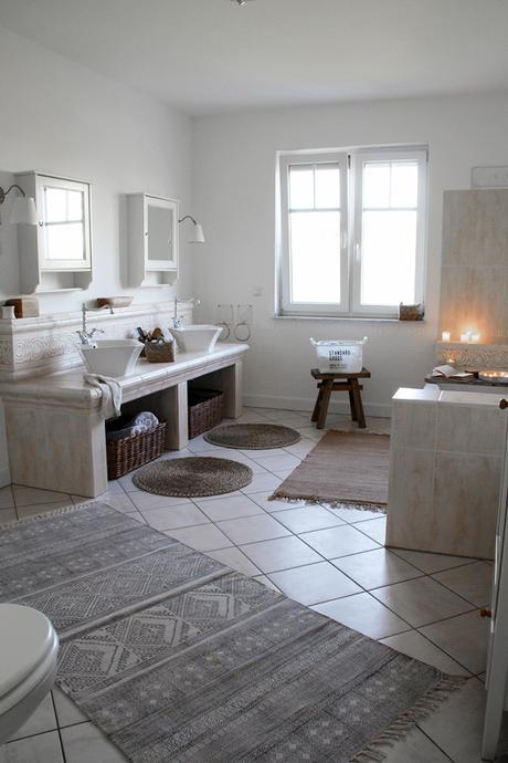 großzügiges Badezimmer mit großer Badewanne und hellen Fliesen, Badezimmer in Holz, Weiß, Ikea Spiegel und Lampen, Teppich House Doctor