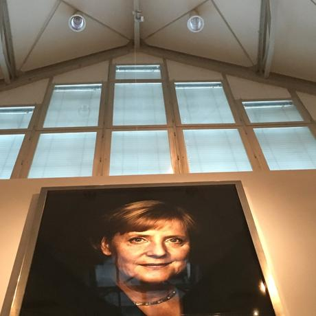 Wie in der DDR: Angela Merkel,Schutzpatronin und Staatsikone der Deutschen wacht über der Ausstellung