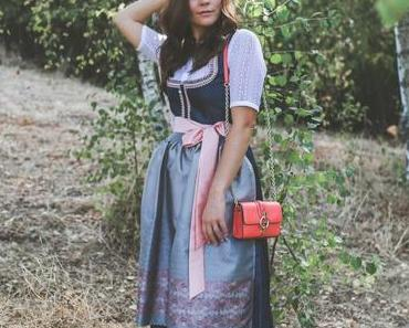 Oktoberfest Outfit: Wiesn Look mit dunkelblauem Dirndl, Spitzenbluse und DVF Bag
