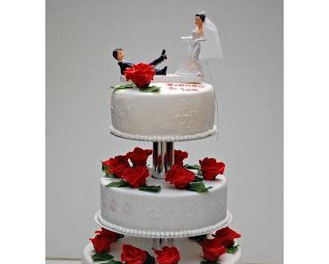 Hochzeitstorte mit roten Rosen auf Tortenständer