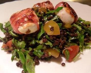 Ein Salat von Belugalinsen, dazu Ziegenkäse im knusprigen Speckmantel