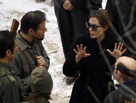 Actress Angelina Jolie (R) talks to actors during the filming of her yet untitled directorial debut in Budapest November 8, 2010. Jolie is directing her first feature film about a Serbian man and Bosnian woman who meet on the eve of the 1992-95 Bosnian war. REUTERS/Laszlo Balogh (HUNGARY - Tags: ENTERTAINMENT)
