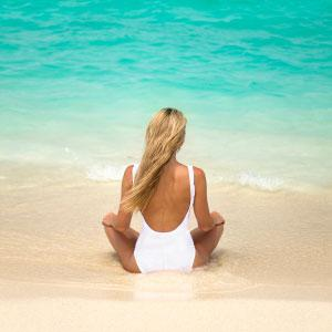 attractive woman relaxing on the shoreline of a tropical beach