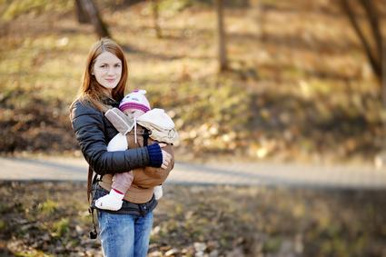 Young mother and her baby in a carrier